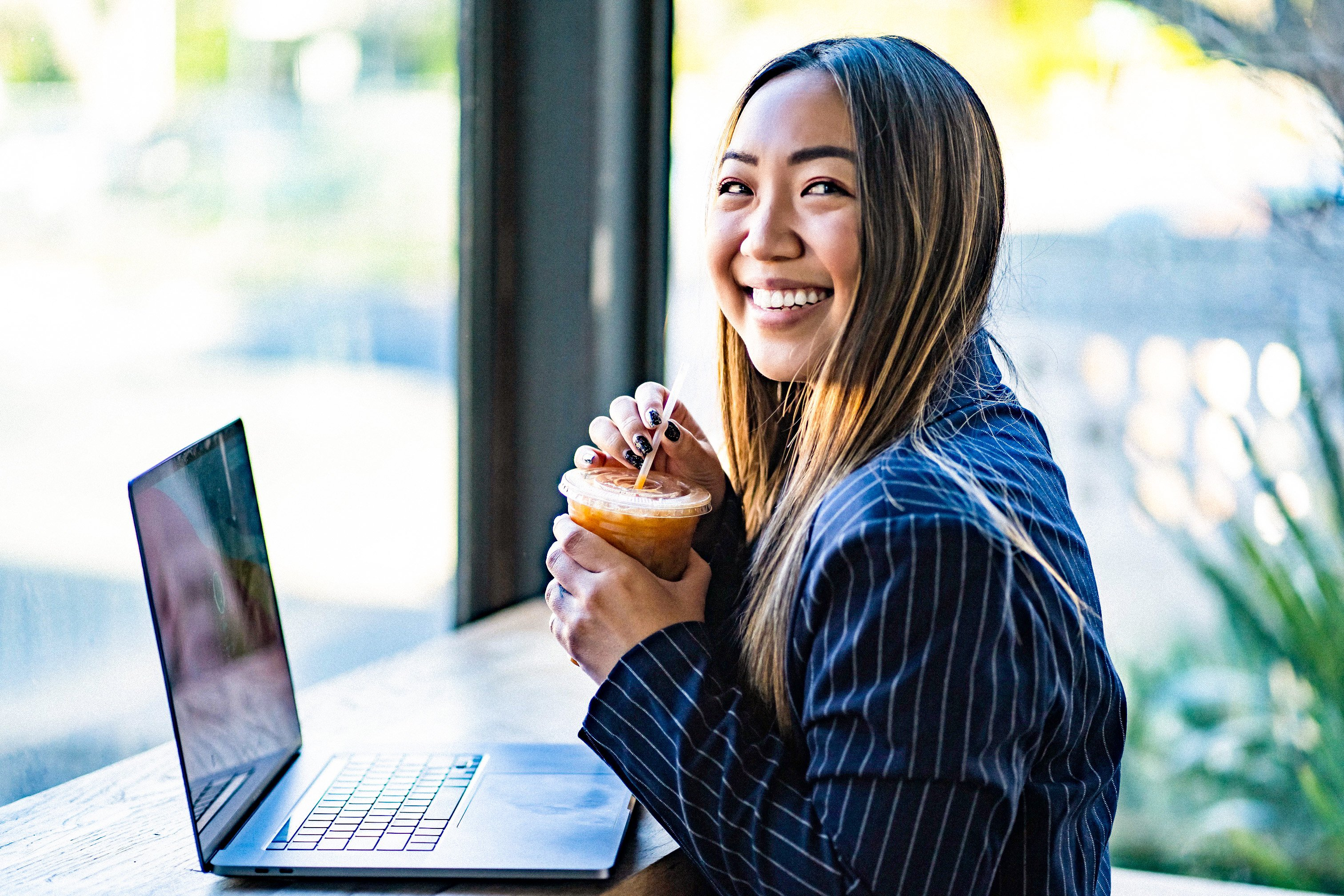 Jenn Hanft CEO and Founder of JOUHCO sipping iced coffee while working