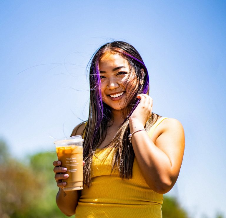 Jenn Hanft CEO and Founder of JOUHCO - Personality-driven Copywriter for multi-passionate entrepreneurs - smiling with nitro cold brew